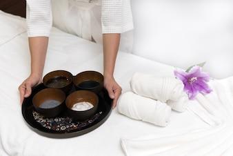 Handen van gelukkige vrouw met spa gezichtsmasker