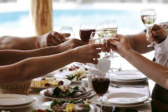 Handen van mensen met een glas champagne of wijn, vieren en roosteren ter ere van de bruiloft of andere viering.