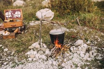 Het beeld van een vuur in het bos waarop brouwpot is