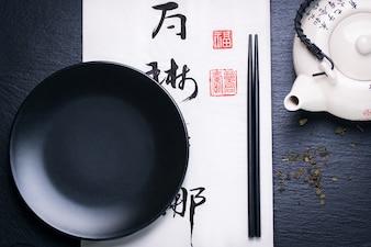 Het voedsel van Azië samenstelling met Chinese stokjes en lege plaat op een donkere steen achtergrond
