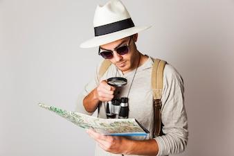 Hipster man kijken naar kaart met vergrootglas