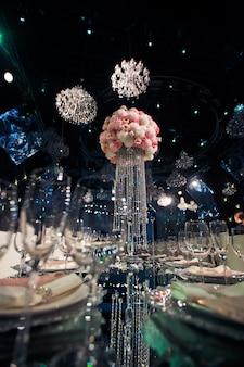 Hoog middenpunt van roze bloemen en kristallen kettingen staat op tafel