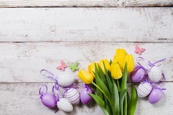 Houten achtergrond met gele tulpen en paaseieren
