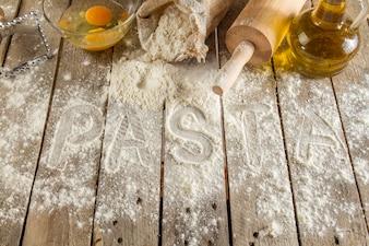 Houten achtergrond met pasta ingrediënten