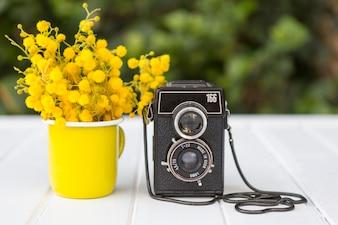 Houten oppervlak met gele bloemen en vintage camera