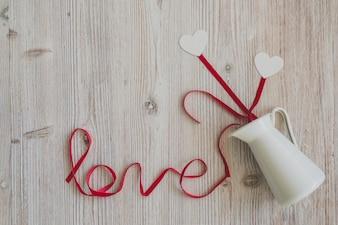 """Houten tafel met het woord """"liefde"""" en een kruik waaruit harten uit te komen"""