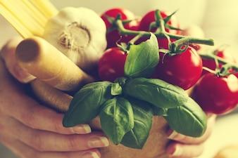 Ingrediënten voor het koken van pasta. Tomaten, Vers Basil, Knoflook, Spaghetti. Cook houdt verse ingrediënten voor koken. Toning. Selectieve focus.