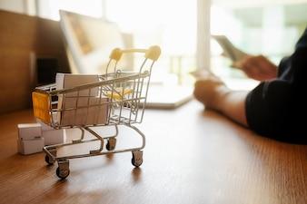 Internet online winkelen concept met laptop en shopping-cart.Vintage tone retro filter effect, zachte focus (selectieve focus)