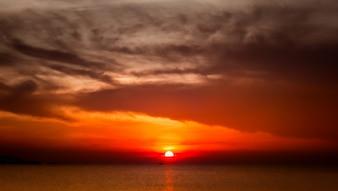 Jacht varen tegen volle rode zonsondergang. Vakantie lifestyle landschap met skyline.