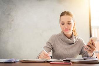 Jong aantrekkelijk meisje praten over de mobiele telefoon en glimlachen terwijl ze alleen in de koffiezaal zit in de vrije tijd en werken op tabletcomputer. Gelukkig wijfje met rust in cafe. Lifestyle