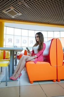 Jong meisje zittend op een oranje sofa te kijken naar de mobiele