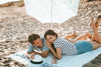 Jong paar liggend op het strand