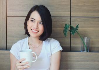Jonge gelukkige vrouw in casual kleding ontspannen op bed tijdens het drinken van thee of koffie, lifestyle en wellness concept