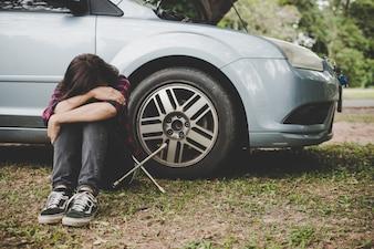 Jonge hipster vrouw wacht op wegenhulp nadat haar auto afgebroken is aan de kant van de weg die tegen haar auto zit.