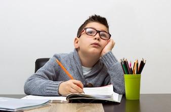Jonge jongen gefrustreerd over huiswerk, thuis schrijven. Jongen studeert aan tafel. Kid tekening met een potlood.