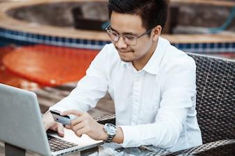 Jonge Knappe man geniet van online winkelen op mobiele telefoon met creditcard.