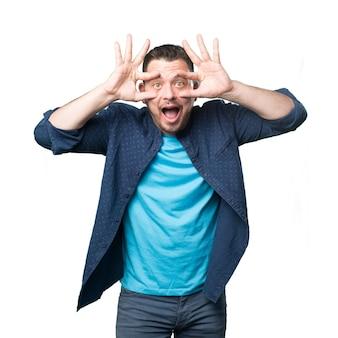 Jonge man draagt een blauwe outfit. Op zoek grappig.