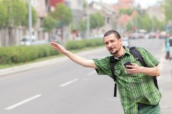 Jonge man met een rugzak taxi stopt
