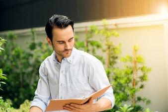 Jonge man op een zomerdag een boek lezen in het park.