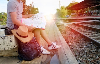 Jonge man reiziger met rugzak en hoed op het treinstation met een reiziger, reizen en recreatie concept