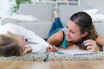Jonge moeder en dochter in huis op het notitieboekje.