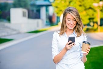 Jonge slimme professionele vrouw lezen met behulp van de telefoon. Vrouwelijke zakenvrouw het lezen van nieuws of sms sms op de smartphone terwijl koffie op pauze uit het werk wordt gedronken.