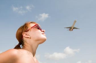 Jonge vrouw kijkt naar een vliegtuig