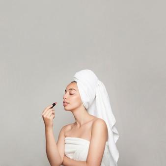 Jonge vrouw schilderen haar lippen