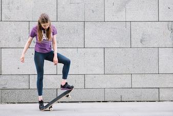 Jonge vrouw staande met skateboard