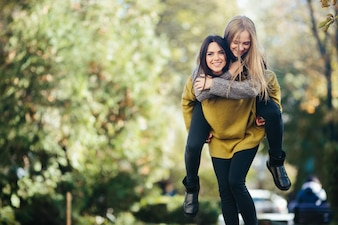 Jonge vrouwelijke vrienden die plezier hebben in het park