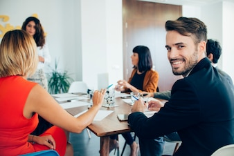 Jonge zakenman glimlachend op de vergadering