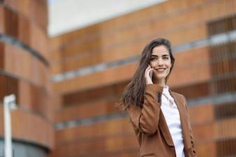 Jonge zakenvrouw praten met een smartphone in de stedelijke achtergrond. Mooie vrouw met formele slijtage met behulp van slimme telefoon.