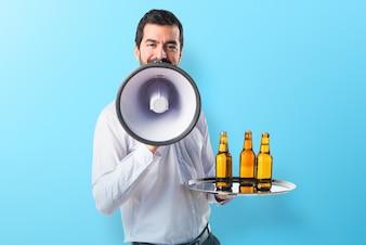 Kelner met bierflessen op de lade die door megafoon op kleurrijke achtergrond schreeuwen