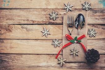 Kersttafel plaats instelling en zilverwerk, sneeuwvlokken, dennenkegels op houten achtergrond met ruimte.