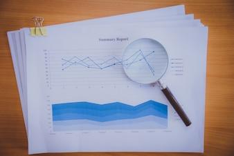 Kijkend naar groeikaart met vergrootglas. Grafieken, grafieken en vergrootglas.