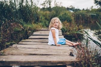 Klein meisje zittend op een houten pier
