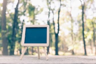 Kleine A-frame blackboard met leeg gebied voor tekst of bericht op rustieke houten tafel in de ochtend tijd