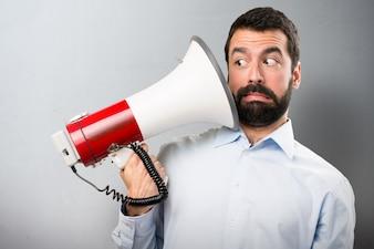 Knappe man met baard met een megafoon op getextureerde achtergrond