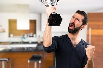Knappe man met baard met een trofee in huis