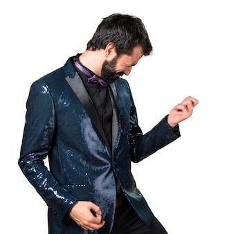 Knappe man met sequin jas die gitaargebaar maakt