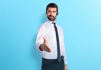 Knappe telemarketer man die een overeenkomst op kleurrijke achtergrond maakt