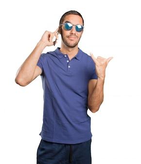 Koele jonge man met behulp van een mobiele telefoon op een witte achtergrond