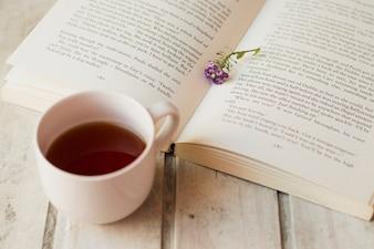 Koffie en open boek met bloem binnen