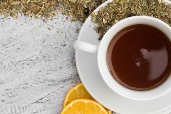 Kopje thee met citroen en droge kruiden op houten achtergrond