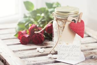 Kruik van het glas met marshmallows en een hart met een tang