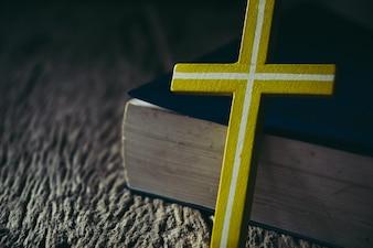 Kruis met heilige Bijbel op houten achtergrond.