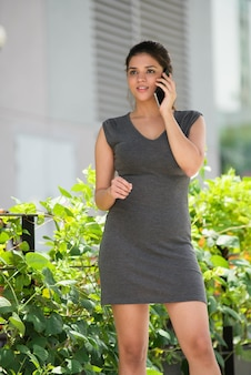 Lachende jonge zakenvrouw praten over de telefoon