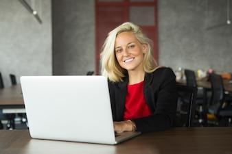 Lachende jonge zakenvrouw werken op laptop