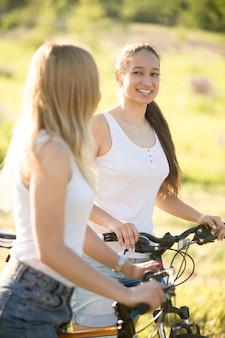 Lachende meisjes rijden fiets
