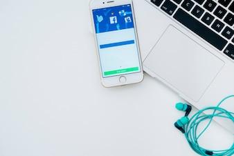 Laptop, telefoon, koptelefoon en facebook